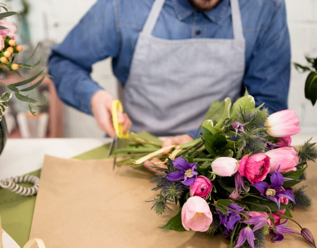 close-up-male-florist-cutting-paper-wrapping-flower-bouquet