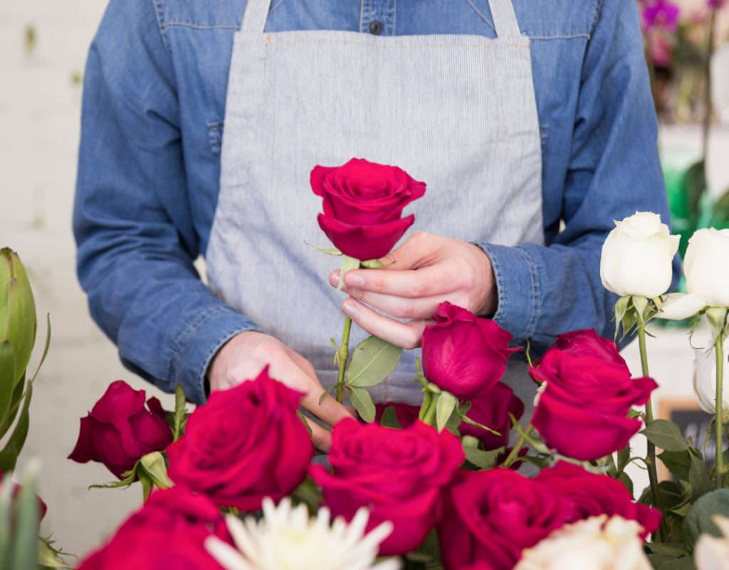 mid-section-male-florist-arranging-rose-flower-bouquet